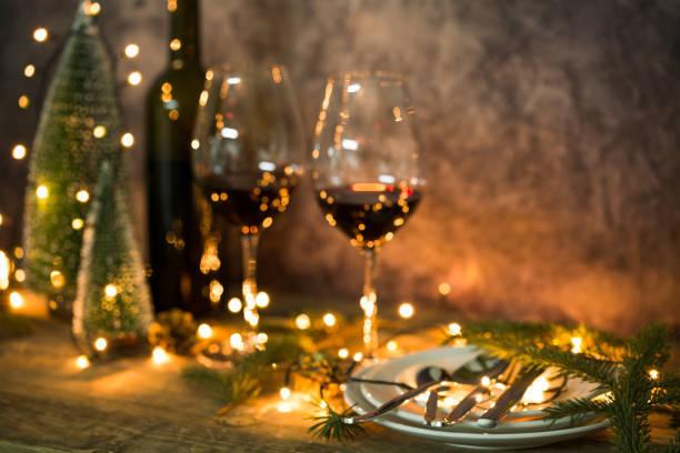 クリスマスライトとテーブルの上に赤ワインのクローズアッ...