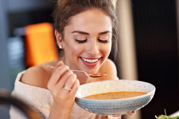 大人の女性が台所でカボチャのスープを食べる