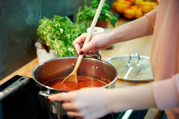 Woman cooking tomato soup i...