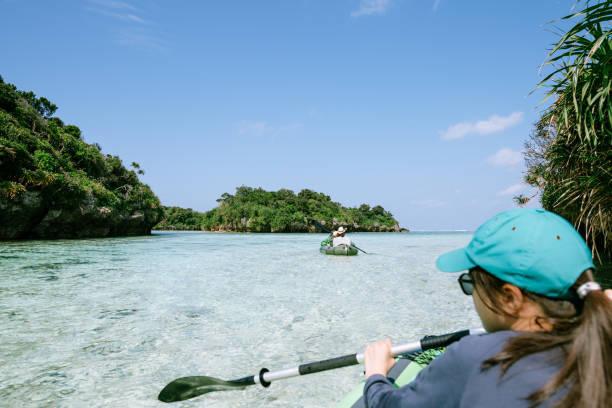 Girl paddling kayak on clea...