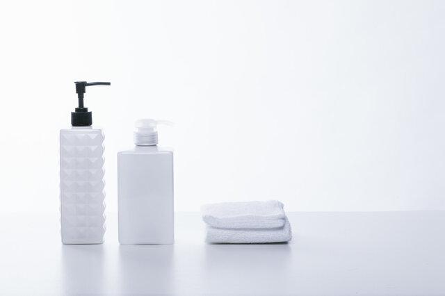 シャンプー用の容器とタオルの写真素材