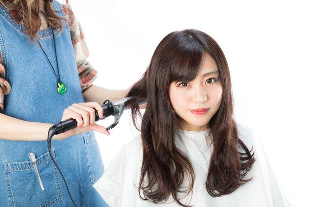 後ろ髪を巻く美容師の写真素材