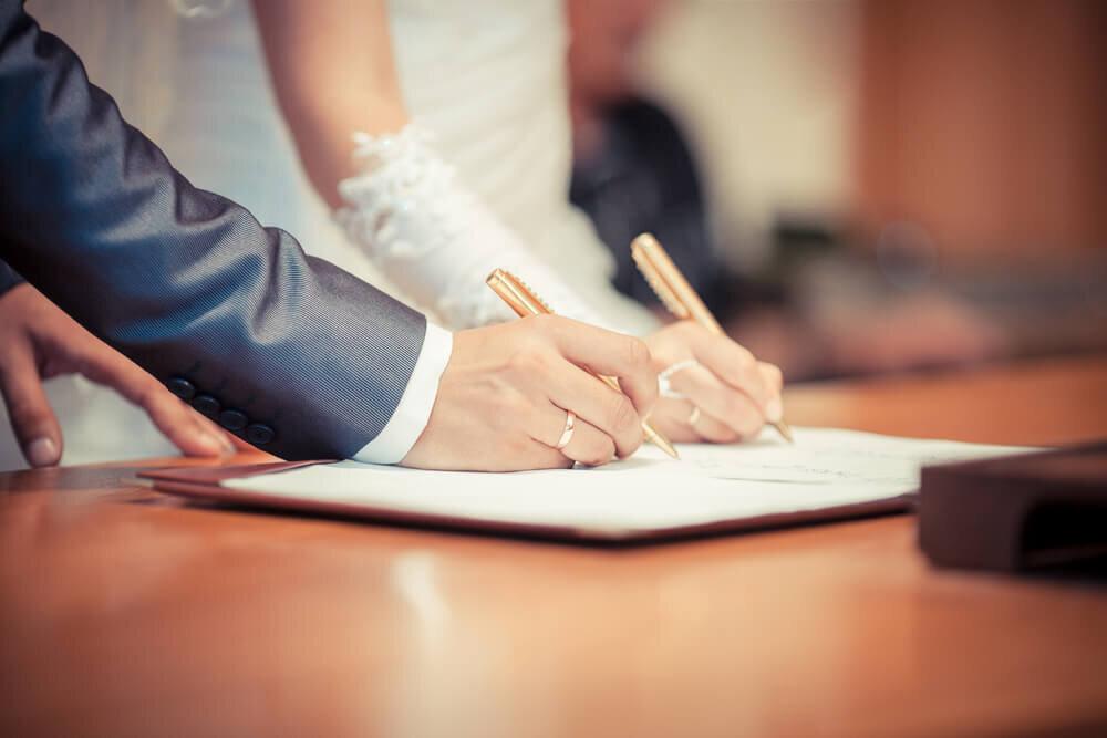 結婚証明書に署名する新郎新婦