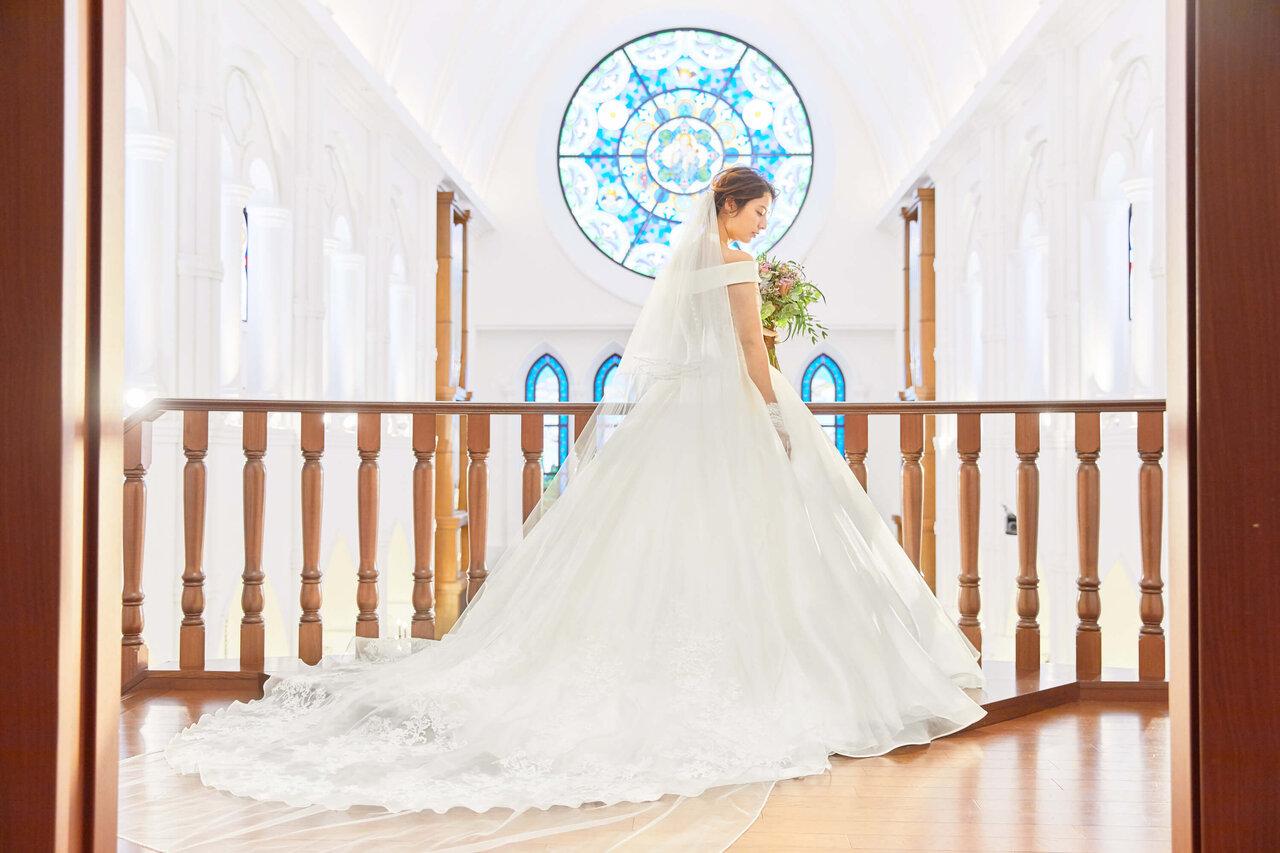 アルカンシエル luxe mariage 大阪の大聖堂(チャペル)のフォトスポットの前に立つ花嫁