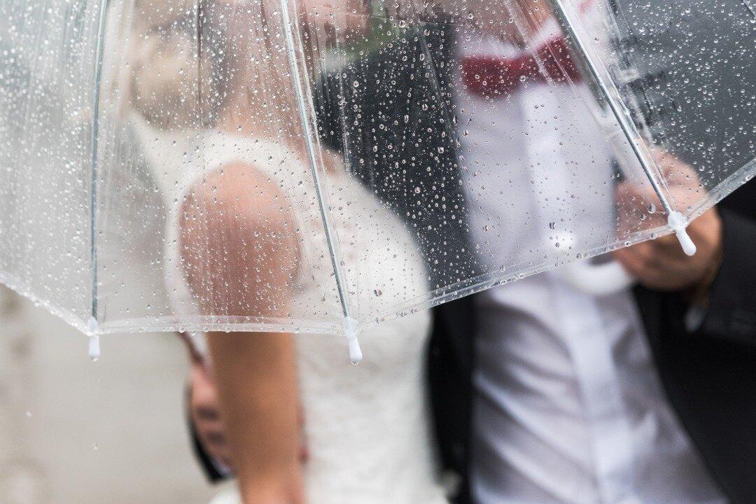 傘をさす新郎新婦