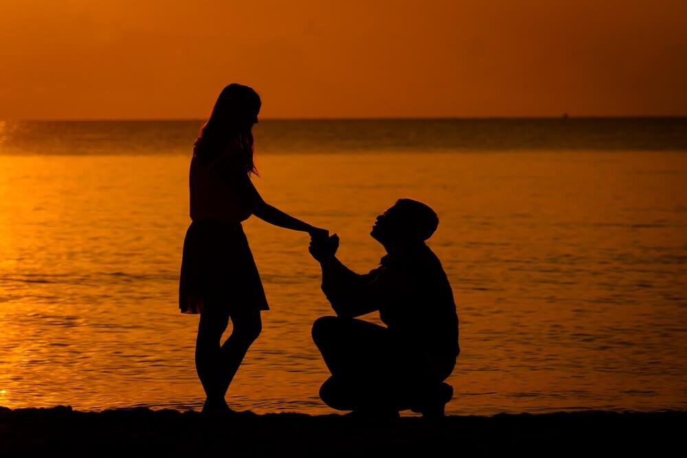 海辺でひざまずいてプロポーズする男性