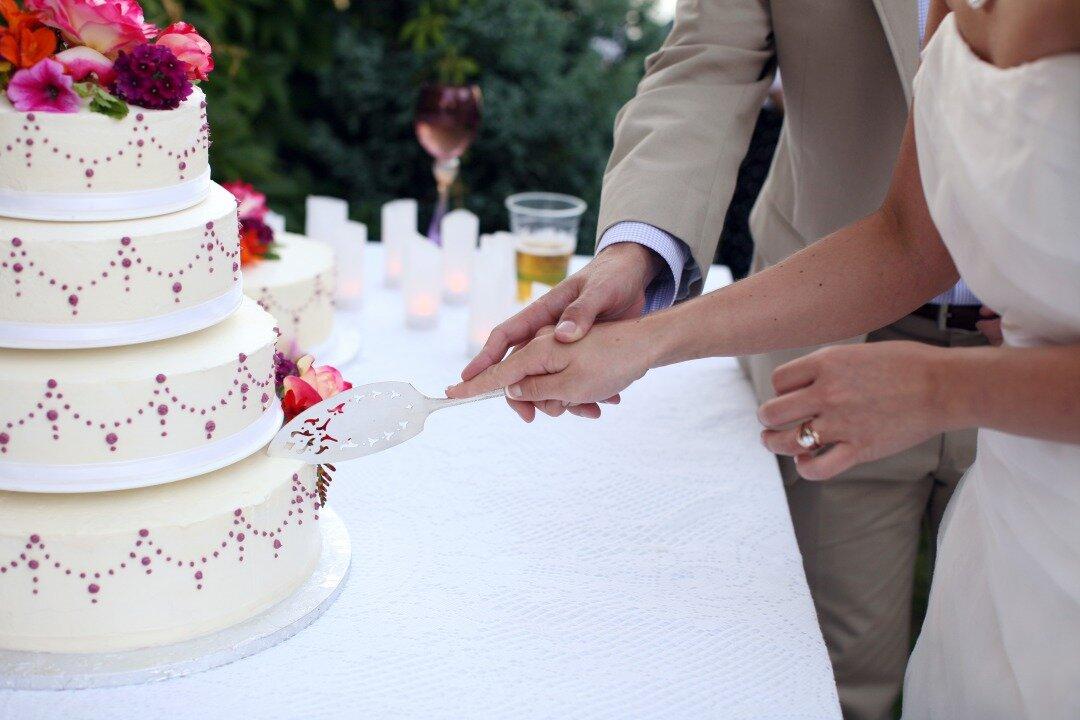 ウエディングケーキ入刀を行っている新郎新婦の様子