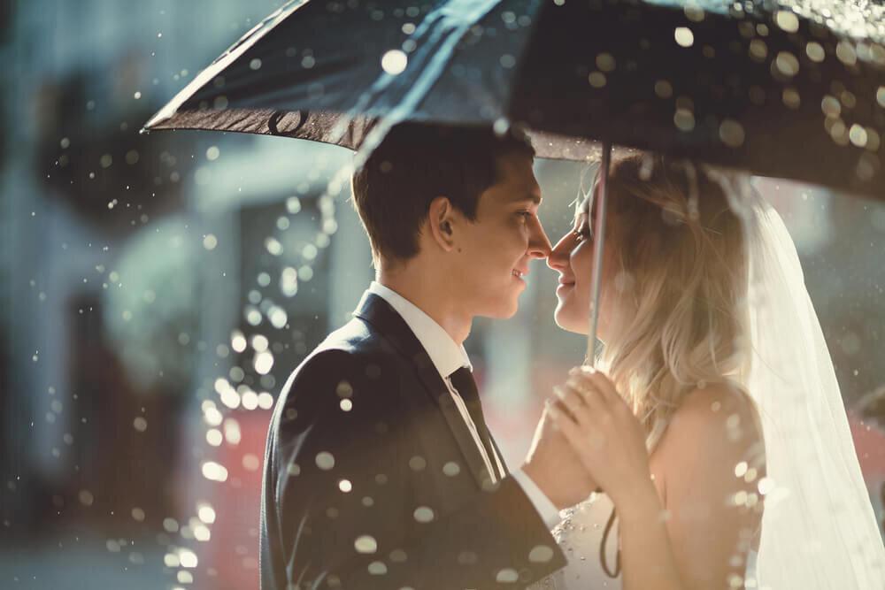傘の下で見つめ合う新郎新婦