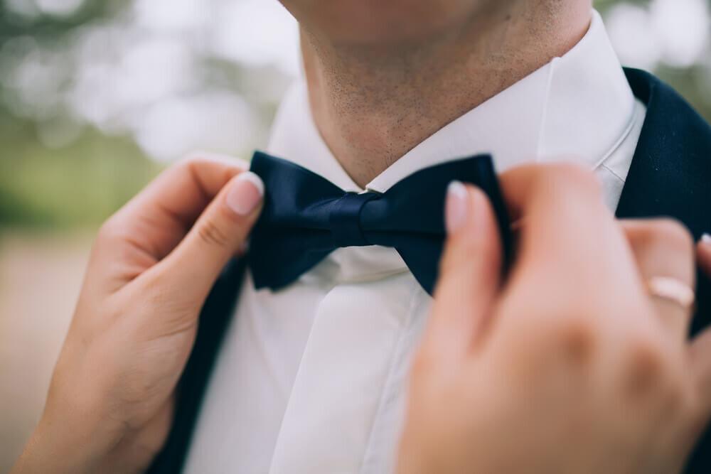蝶ネクタイをつける新郎