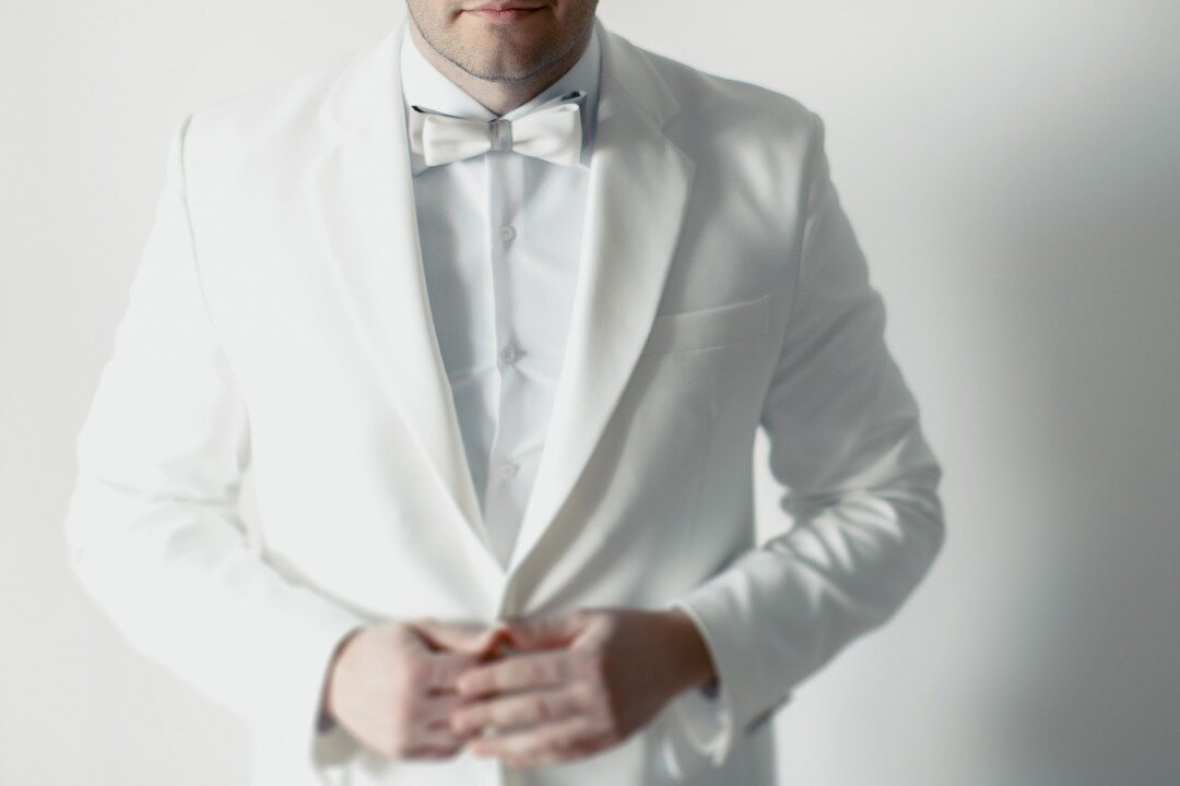白いタキシードを着ている新郎