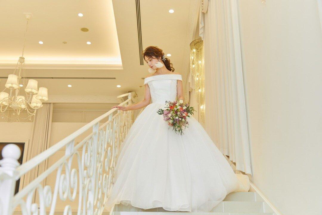 プリンセスラインのウエディングドレスをきた階段を下りる花嫁