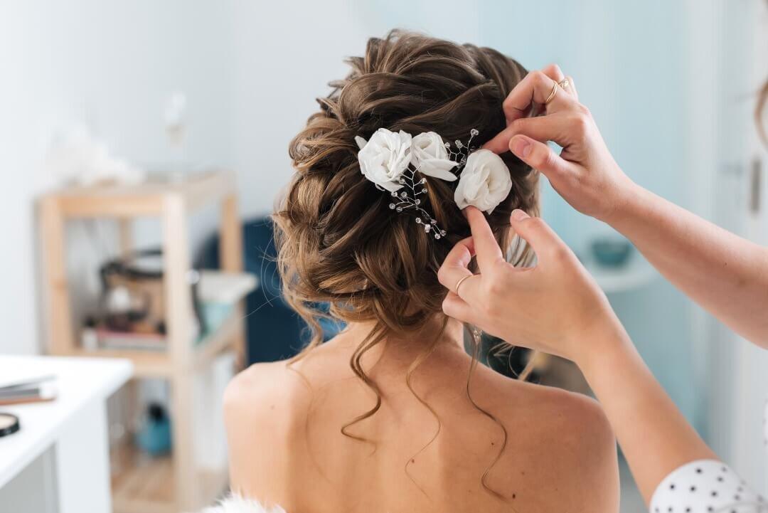 バラの髪飾りを付ける花嫁