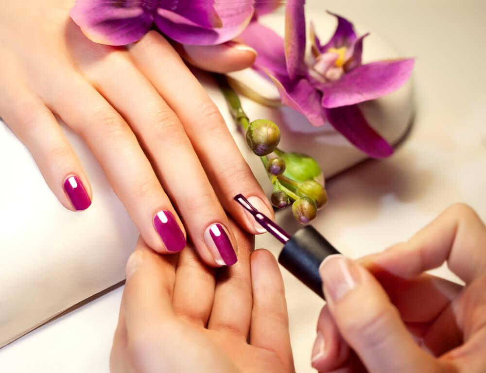 紫のマニキュアを塗っている爪