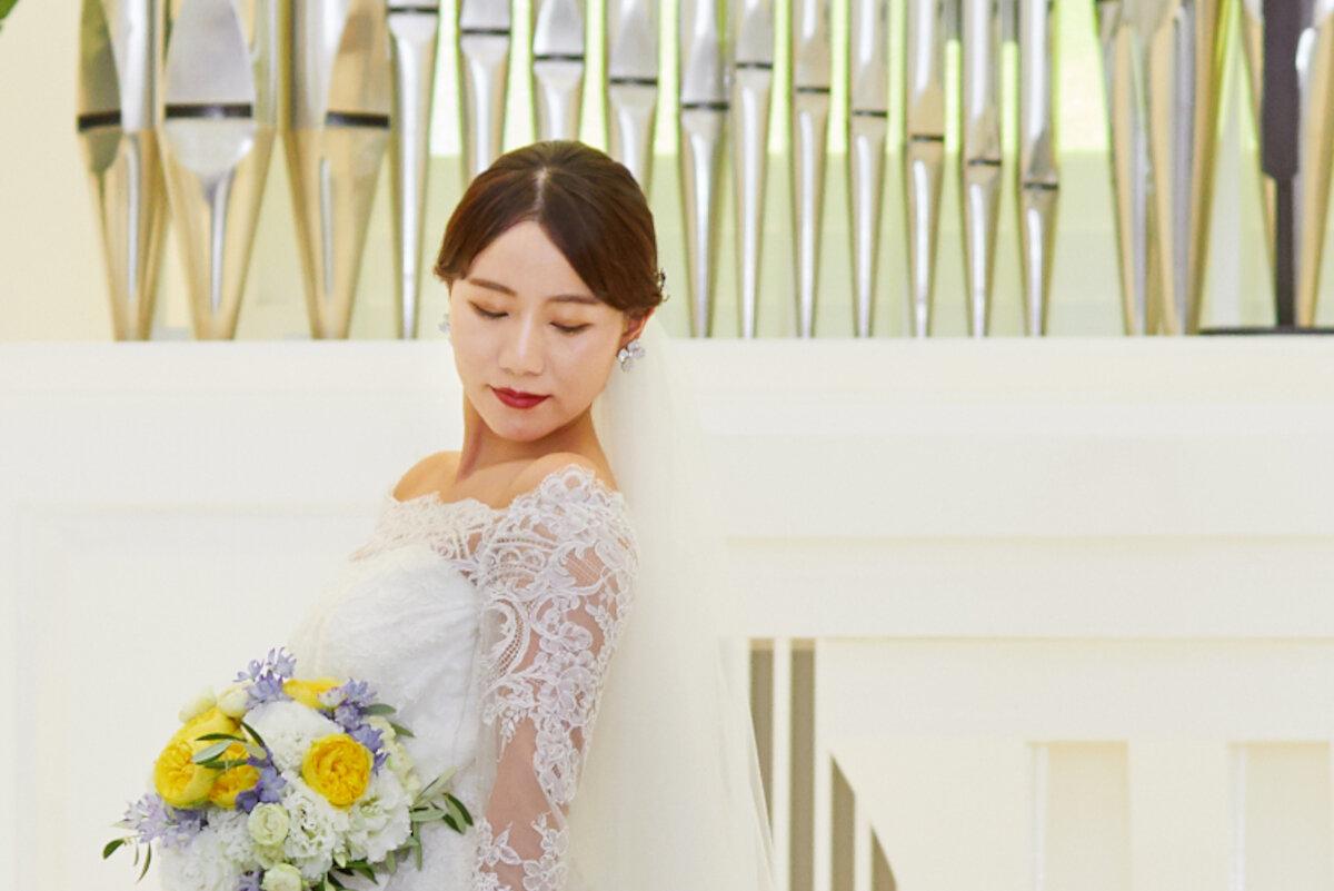 タイトシニヨンスタイルでチャペルに立つ花嫁