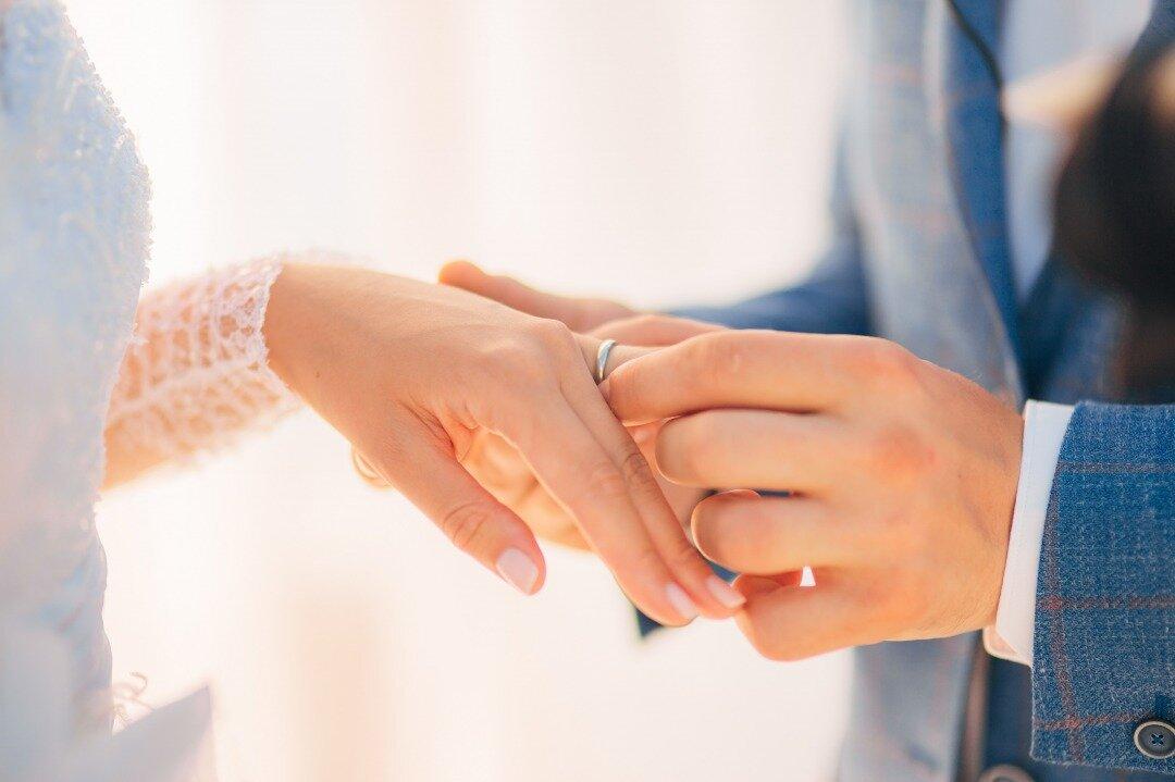 新婦の左薬指に結婚指輪をはめている新郎の様子