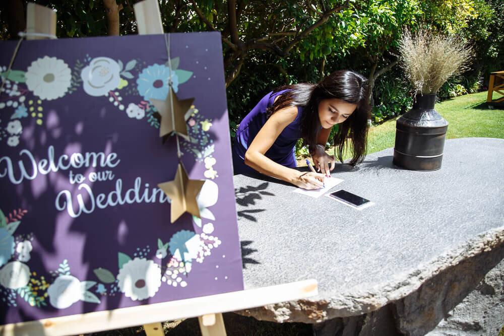 ウエルカムボードの近くでメッセージを書く女性