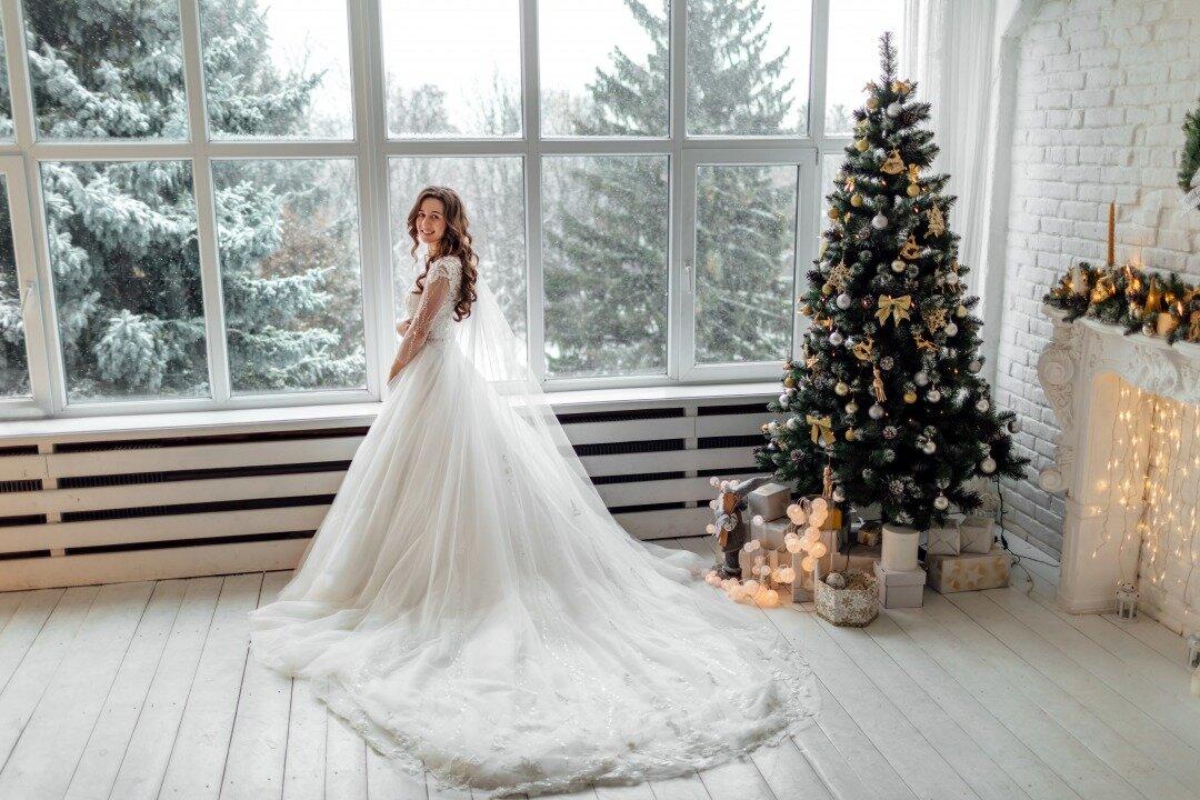クリスマスツリーの横でほほ笑む花嫁