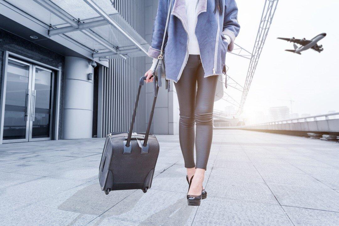 スーツケースを持って空港を歩く女性