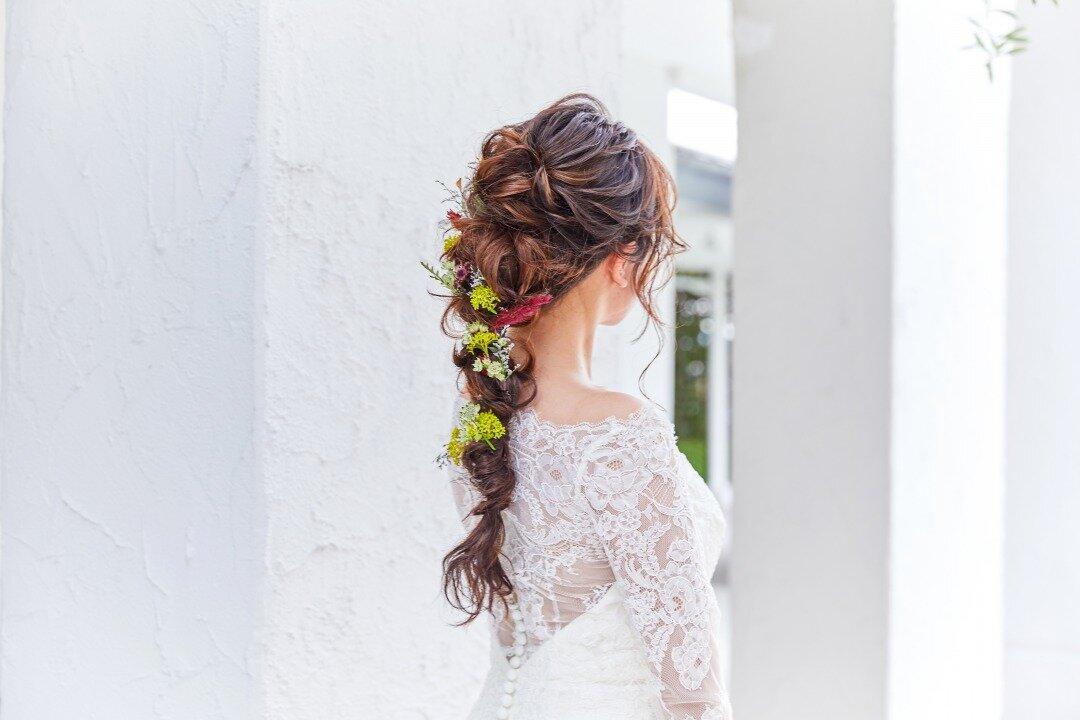 花を散りばめたダウンスタイルの髪型をした花嫁