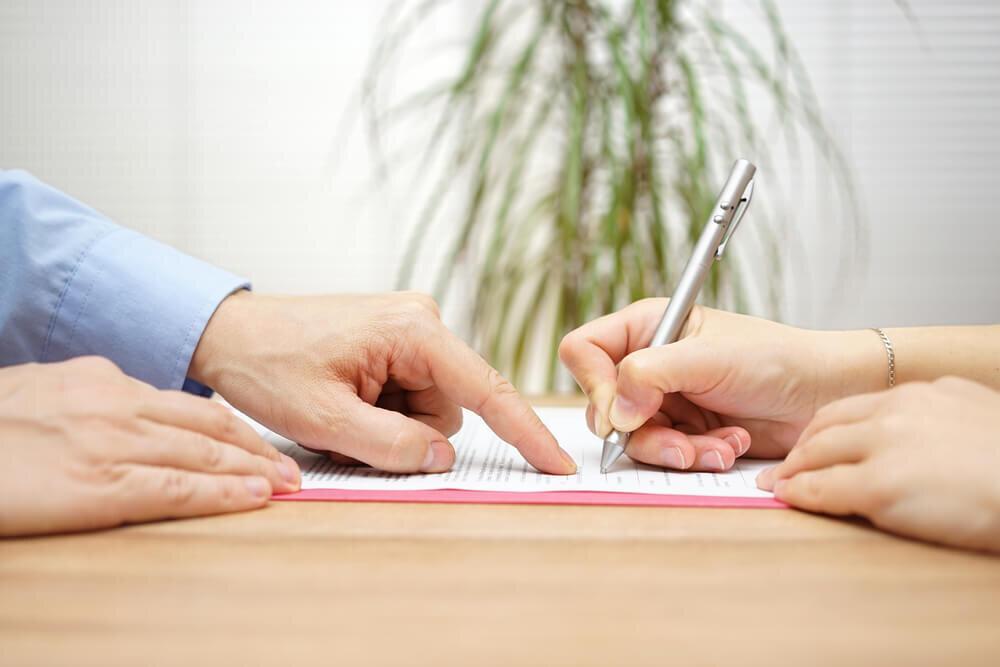 書類の書き方を女性に説明する男性