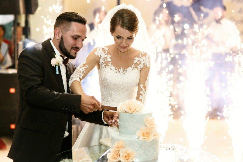 白いケーキを切る新郎新婦