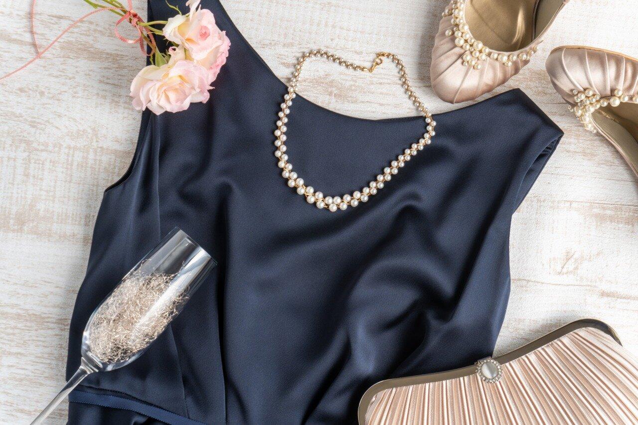 テーブルの上にあるパーティドレスとネックレス