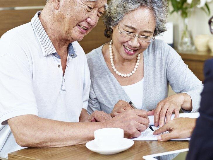 書類にサインをする老夫婦