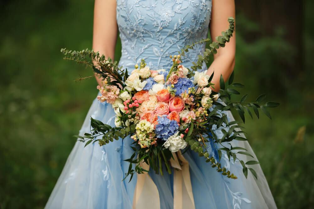 ブルーのドレスを着てブーケを持つ女性