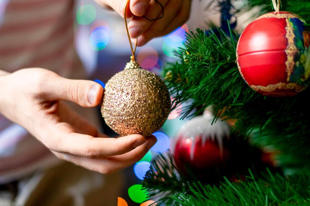 クリスマスツリーの飾りつけをする人