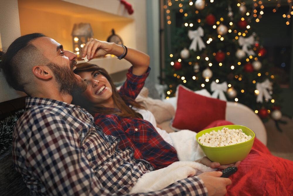 ポップコーンを食べながら映画鑑賞をするカップル