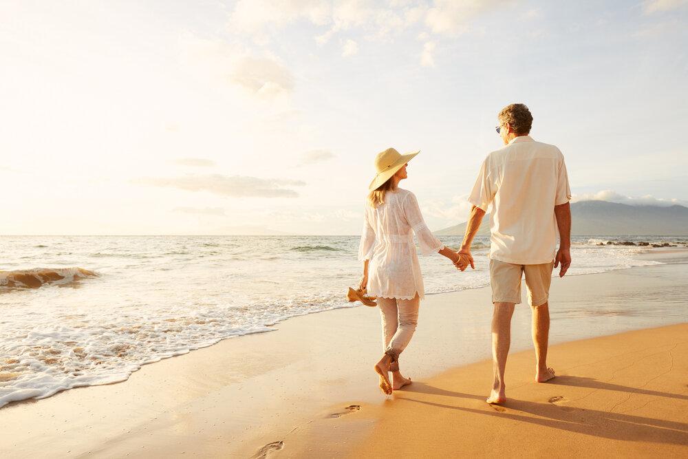 海辺を仲良く歩くカップル