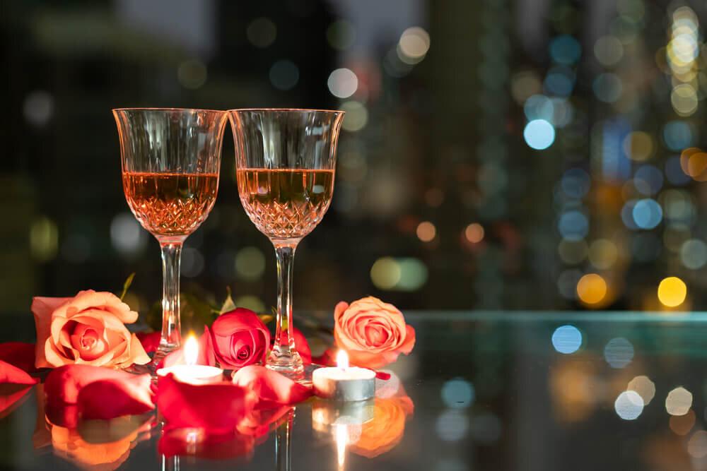 テーブルに置かれたワイングラスとバラ