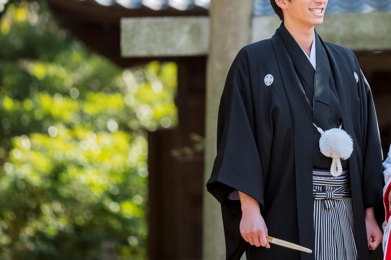 黒五つ紋付き羽織袴を着ている男性