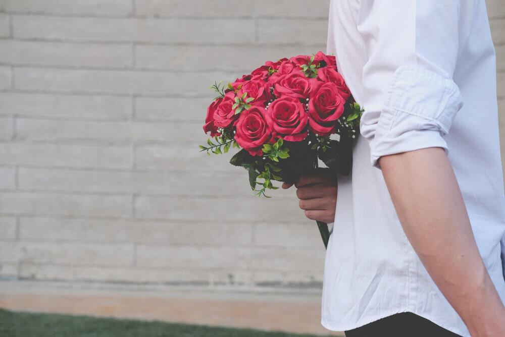 バラを隠し持つ男
