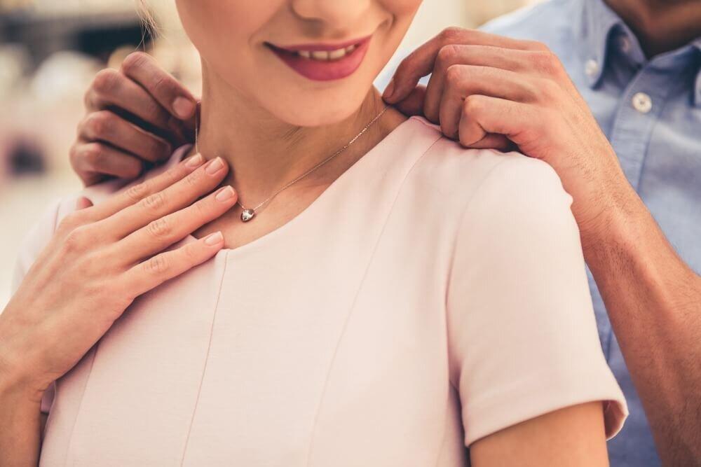 贈られたネックレスを身に着ける女性
