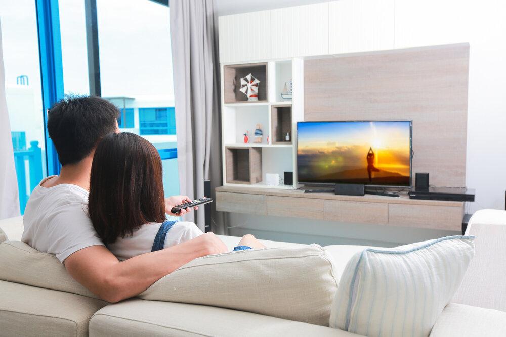 ソファに座りテレビを見るカップル