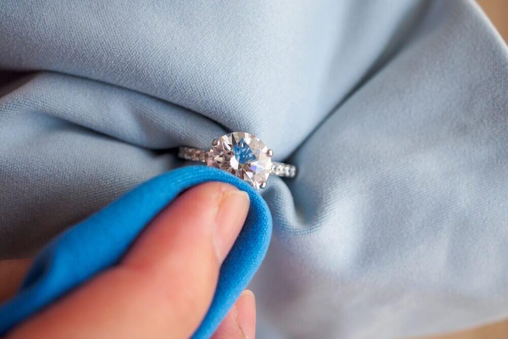 布で婚約指輪をお手入れする人