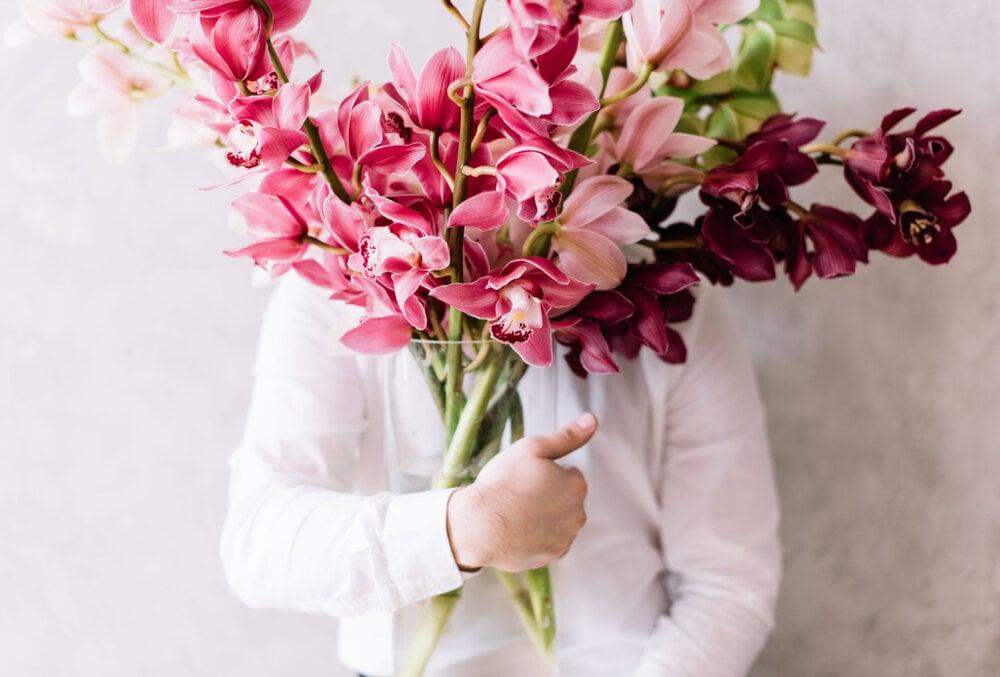 シンビジウムを活けた花瓶を抱える人