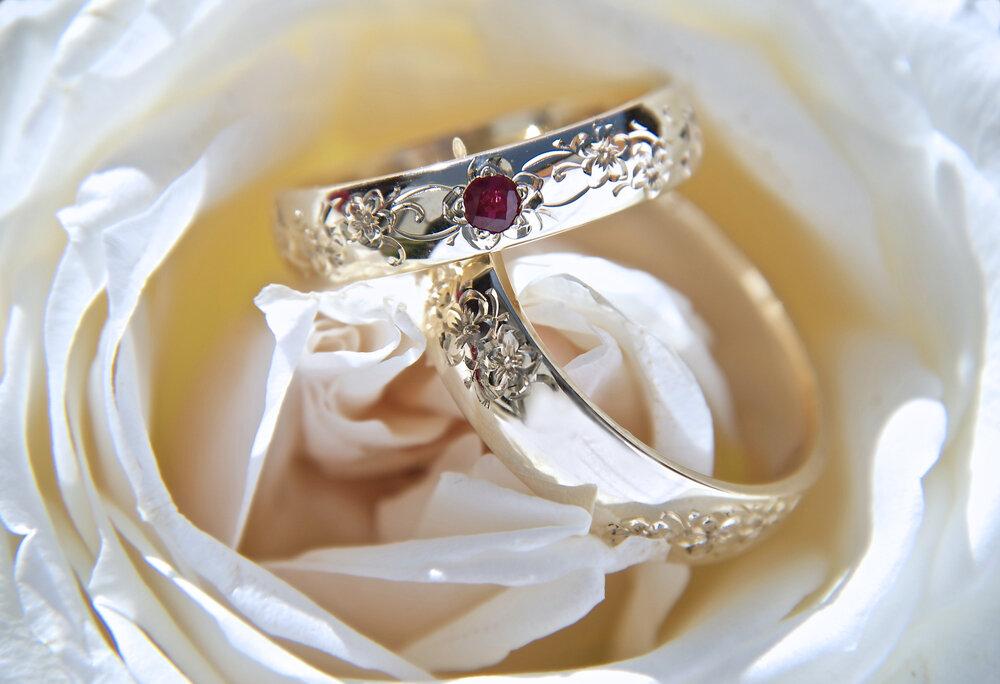白いバラと赤い宝石の入った結婚指輪