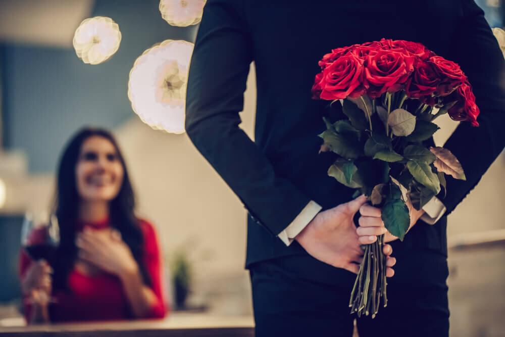 赤いバラの花束を持つ男性