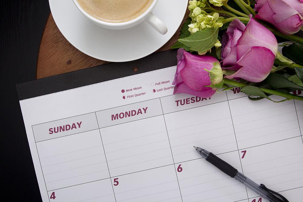 机上のカレンダーとコーヒーと花