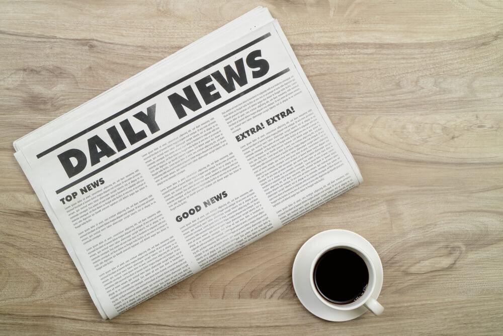 木の机の上にある新聞とコーヒー