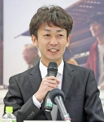 新規調教師試験に合格し、笑顔で質問に答える武幸四郎