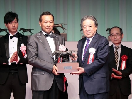 JRAの後藤正幸理事長から記念トロフィーを受け取る里見...