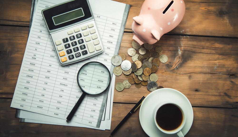 卓上の電卓と豚の貯金箱
